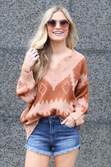 trendy aztec knit sweater tucked into distressed denim shorts
