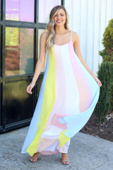 Model wearing the Multi-Colored Striped Maxi Dress in Yellow with trendy sunglasses from dresses boutique online