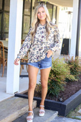 Model wearing the Leopard Ruffle Trim Hoodie in Taupe with denim shorts