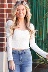 Model wearing the Smocked Eyelet Crop Top in White with light wash jeans