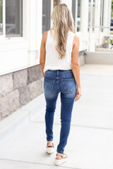 Model wearing the Mid-Rise Distressed Skinny Jeans with white bodysuit and heels from Dress Up Back View