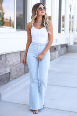 white button up bodysuit styled with pinstripe flare jeans