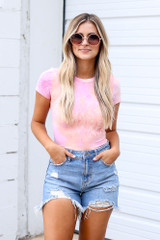 Model wearing the Tie-Dye Bodysuit in Pink with distressed denim shorts
