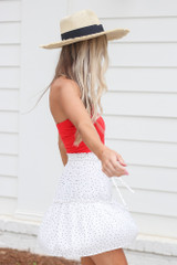 Model wearing the Tiered Polka Dot Skirt in White with a red bodysuit