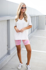 Model wearing the Tie-Dye Biker Shorts in Pink with white sneakers