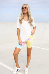 Model wearing the Tie-Dye Biker Shorts in Yellow with white sneakers