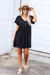Model wearing the Button Front Babydoll Dress in Black with platform espadrilles