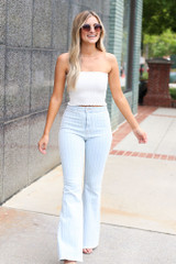 Model wearing the Smocked Bandeau in White with flare jeans