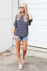 Model wearing the Ruffle Sleeve Tee with distressed denim shorts
