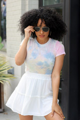 Dress Up model wearing the Tie-Dye Burnout Bodysuit with a white tiered mini skirt