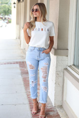 Model wearing the Brunch Graphic Tee with distressed denim jeans and nude heels