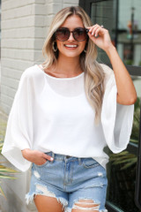 Model wearing the Oversized Blouse with distressed mom shorts