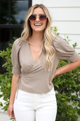 Taupe - puff sleeve wrap blouse styled with white flare jeans at dress up