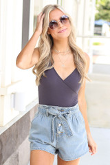 Model wearing the Paperbag Waist Denim Shorts with a wrap bodysuit