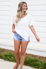 Model wearing the Textured Oversized Top with denim shorts