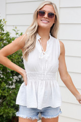 Model wearing the High Neck Smocked Tank in White with denim shorts