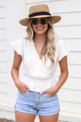 Model wearing the Crochet Peplum Top in White with a straw sun hat