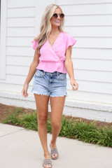 Model wearing the Crochet Peplum Top in Pink with distressed denim shorts