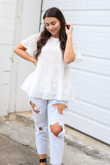 Model wearing the Eyelet Tiered Babydoll Top in White with distressed jeans