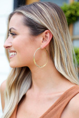 Model wearing the Twisted Hoop Earrings in Gold