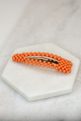 Flat Lay of the Beaded Hair Clip in Orange