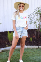 Model wearing the Vacay Graphic Tee with denim shorts and a straw sun hat