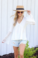 Model wearing the Waffle Knit Babydoll Top with distressed denim shorts