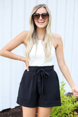 Model wearing the Paperbag Waist Shorts in Black with a white tank