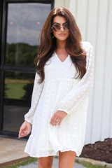 Model wearing the Swiss Dot Babydoll Dress in White with round sunglasses