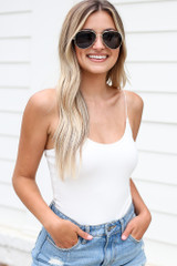White - Model wearing the Cami Bodysuit with distressed denim shorts