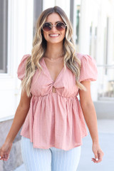 Model wearing the Swiss Dot Babydoll Blouse in Blush with flare jeans