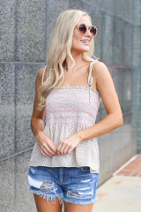 Model wearing the Smocked Peplum Tank in Ivory with denim shorts