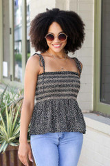 Model wearing the Smocked Peplum Tank in Black with flare jeans