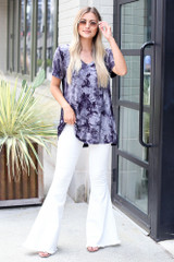 Model wearing a Tie-Dye Tee with white flare jeans