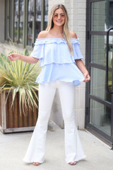 Model wearing the Ruffled Top in Light Blue with white flare jeans
