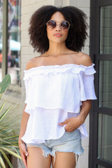 Model wearing the Ruffled Top in White with denim shorts