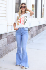 Dress Up model wearing the Kind Graphic Tee with flare jeans