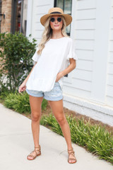 Model wearing the Ruffle Hem Tunic with denim shorts and sandals
