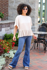 Model wearing the Peplum Top with flare jeans