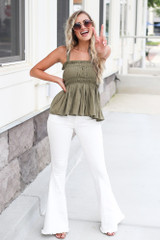 Model wearing the Smocked Peplum Tank in Olive with white flare jeans