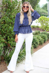 Model wearing the Polka Dot Long Sleeve Blouse with white flare jeans