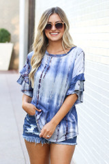 Model wearing the Tie-Dye Ruffle Sleeve Top with distressed denim shorts