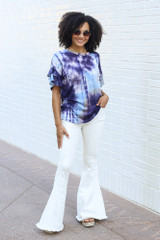 Model wearing the Tie-Dye Ruffle Sleeve Top with white flare jeans