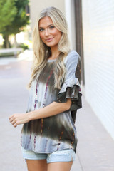 Model wearing the Tie-Dye Ruffle Sleeve Top with distressed denim mom shorts