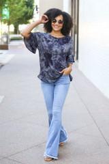 Model wearing the Tie-Dye Ruffle Sleeve Top with light wash flare jeans