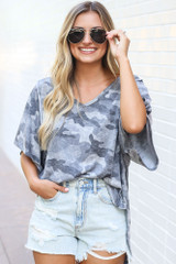 Model wearing the Oversized Camo Top tucked into light wash distressed denim shorts