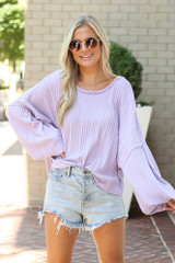 Dress Up model wearing the Oversized Ribbed Knit Top with light wash distressed denim shorts