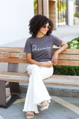 Model wearing the Dreamer Graphic Tee with white flare jeans
