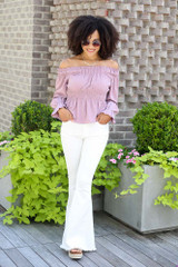 Model wearing the Smocked Off-the-Shoulder Blouse with white flare jeans
