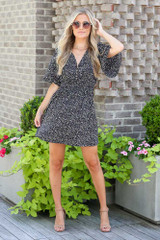 Model wearing the Smocked Floral Dress in Black with nude heels